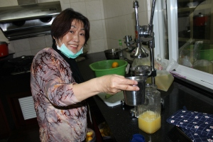 My aunt Dao-Liou proudly squeezing orange juice in her kitchen
